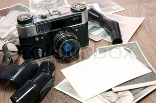 old retro photo camera and film on wooden background
