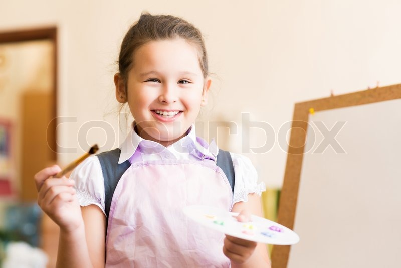 Portrait of Asian girl in apron interested in painting at an art school, stock photo