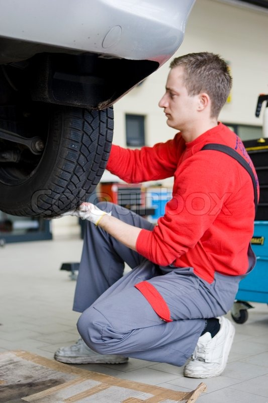 Stock image of 'A male mechanic changing a car's tire'