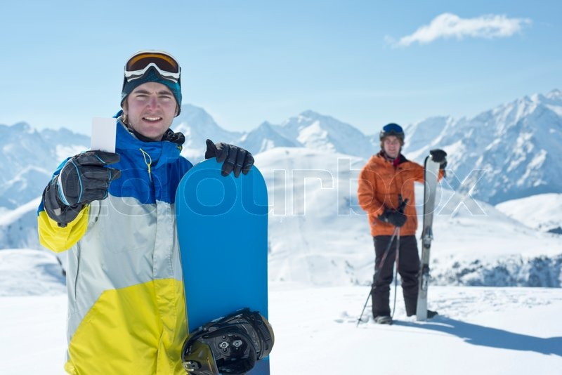 Two man with winter sport equipment looking at camera. One is showing a blank lift pass. Concept to illustrate ski admission fee, stock photo
