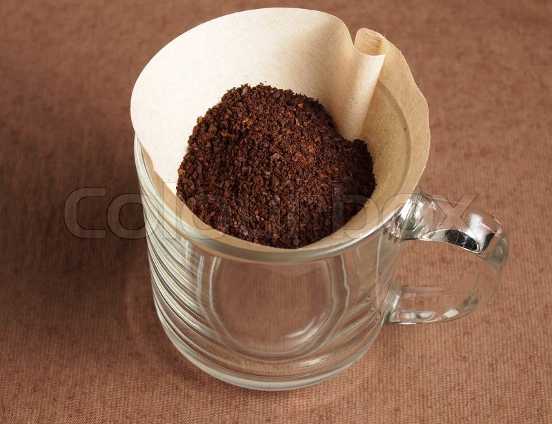 Preparing Grinded coffee crop on paper filter, stock photo