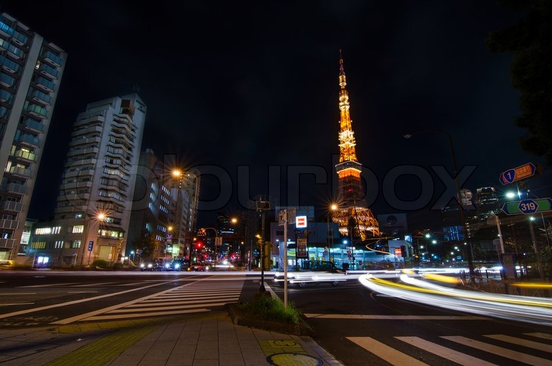 TOKYO, JAPAN - NOVEMBER 28: View of busy street at night with Tokyo Tower in the distance in Tokyo, Japan on November 28, 2013, stock photo