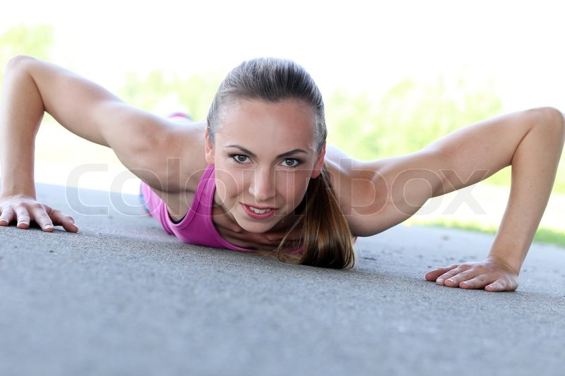 Sport, activity. Cute woman during push-ups, stock photo