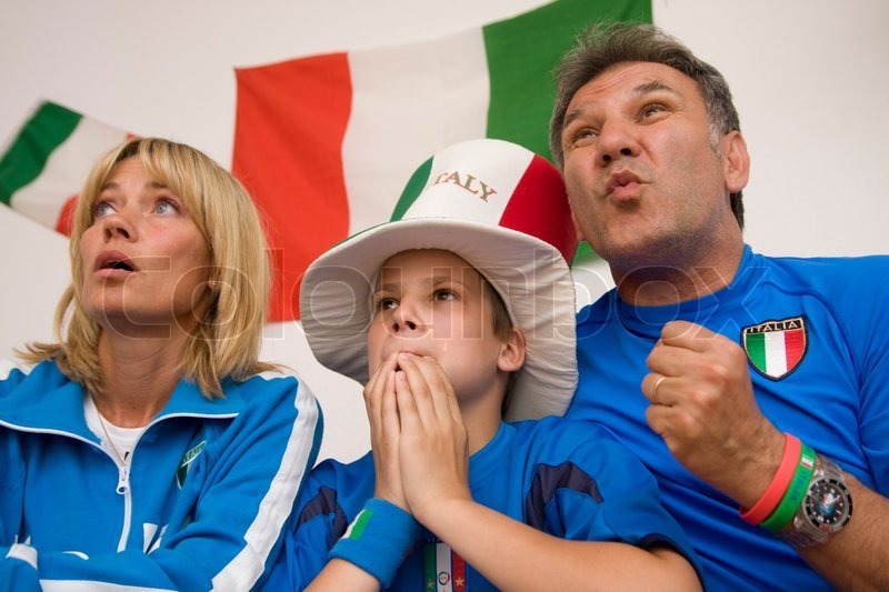 Excited faces of a family watching Italian football, stock photo