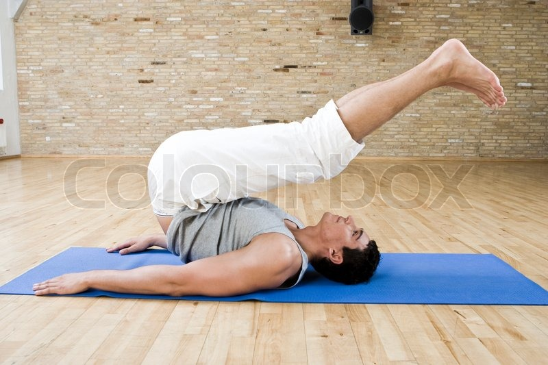 A Man Lifts His Legs On Air During Yoga Class