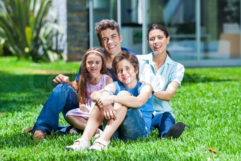 happy family sitting on grass in front of house parents with two children smile stock photo. Black Bedroom Furniture Sets. Home Design Ideas