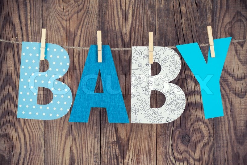 Letters of word baby hanging on clothesline against wooden ...