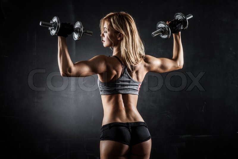 Brutal athletic woman pumping up muscles with dumbbells, stock photo