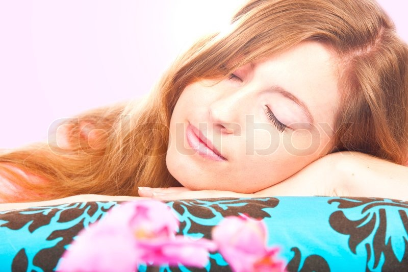 Attractive woman lying on a pillow with eyes closed, stock photo