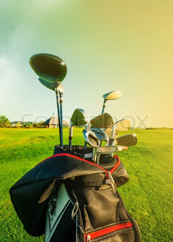 Golf club. Bag with golf clubs Green golf field and ball in grass, stock photo