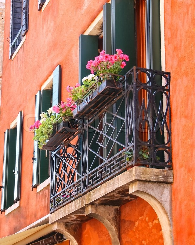 Picturesque balcony with flowers in an old italian house sto.