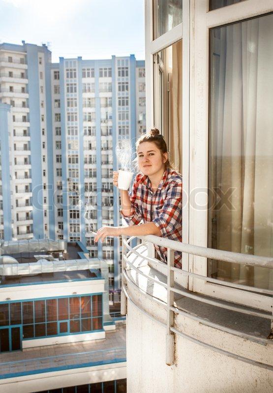 junge frau rauchen und trinken kaffee auf balkon stock foto. Black Bedroom Furniture Sets. Home Design Ideas