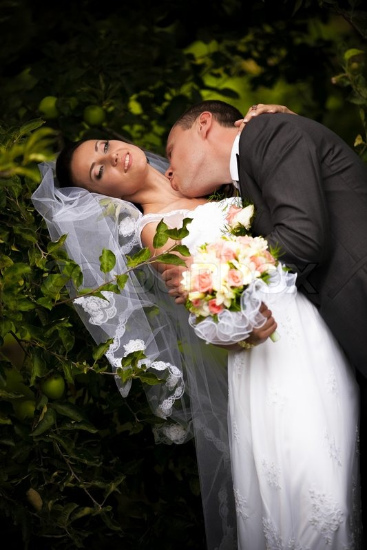 Handsome groom kissing passionately bride in neck