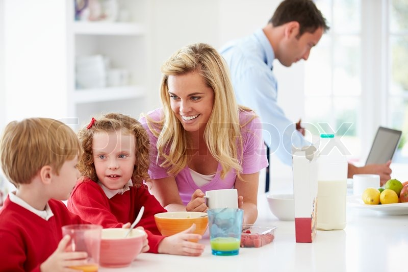 Family Having Breakfast In Kitchen Before School And Work, stock photo