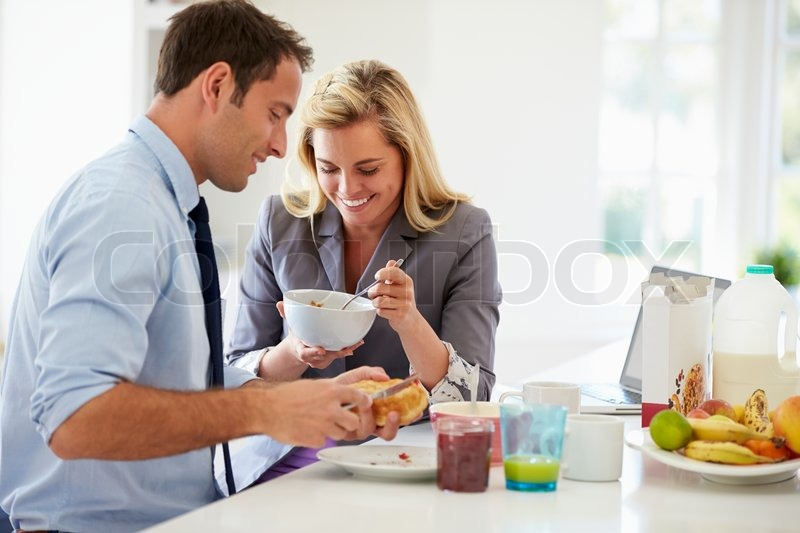 Couple Having Breakfast Together Before Leaving For Work, stock photo