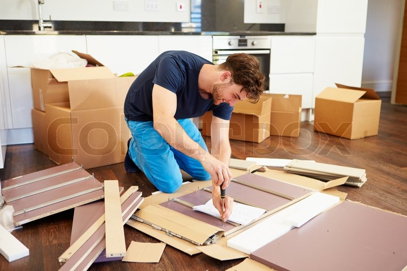Self Assemble Furniture man putting together self assembly furniture in new home | stock