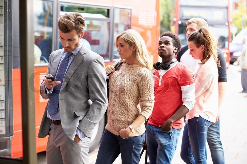 Queue Of People Waiting At Bus Stop, stock photo