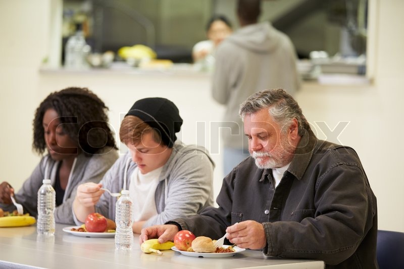 People Sitting At Table Eating Food In Homeless Shelter, stock photo