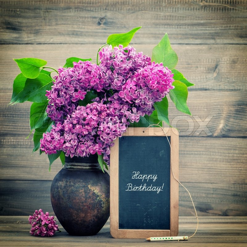 Bouquet of lilac flowers on wooden background. blackboard with ...