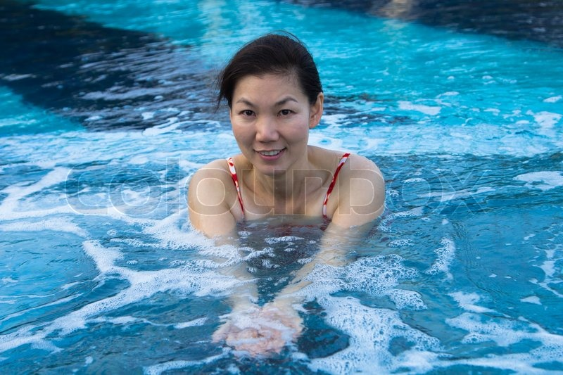Asian woman enjoy and relaxing in spa pool on vacation, stock photo