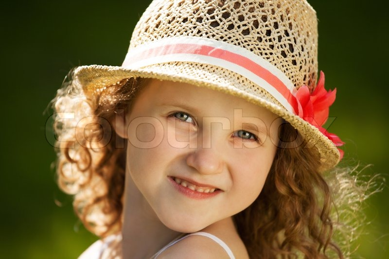 Little happy curly girl in a straw hat, stock photo