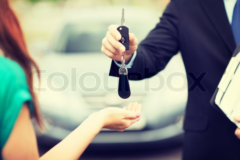 Transportation and ownership concept - customer and salesman with car key outside, stock photo