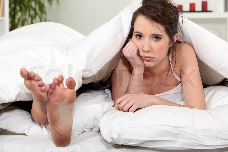 Unhappy woman lying next to her boyfriend\'s feet, stock photo