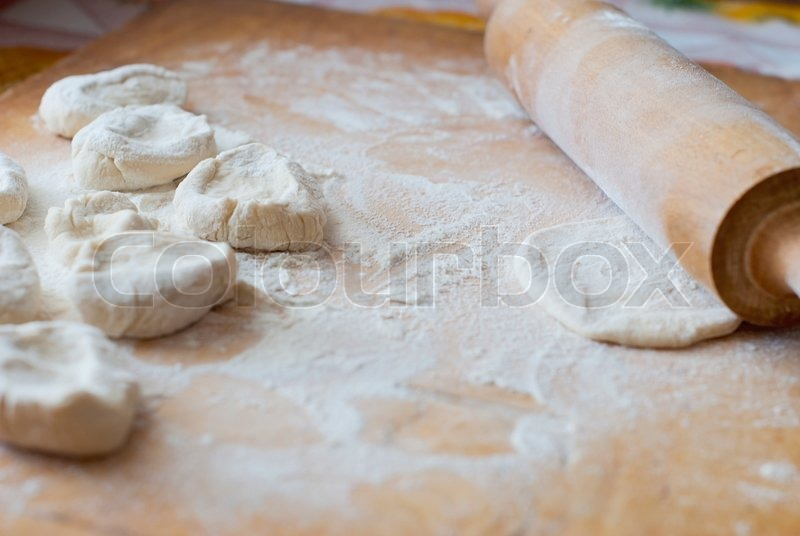 Small pieces of dough with flour on a wooden board with a rolling pin, stock photo