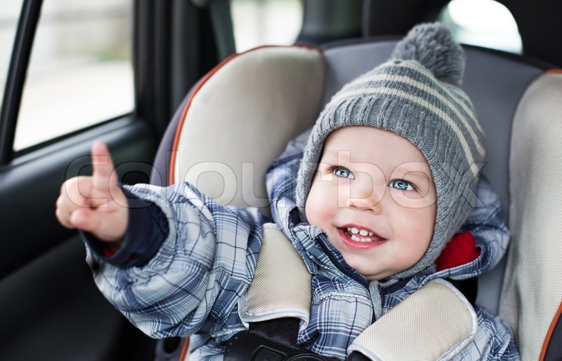 Happy toddler boy sitting in the car seat , stock photo