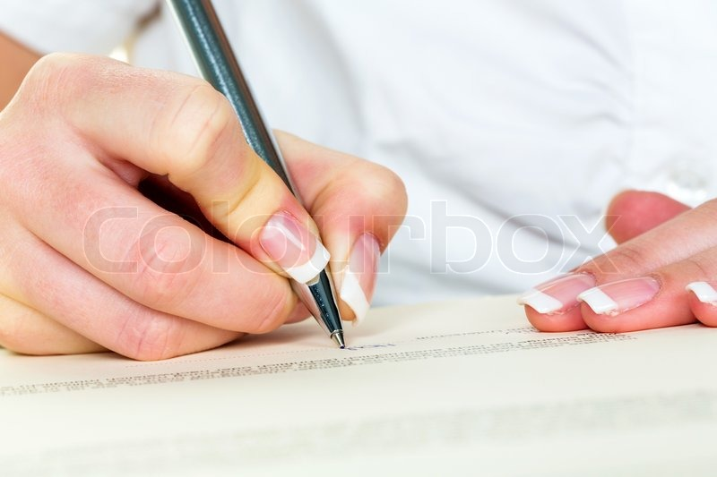 A woman signs a contract or a will with a fountain pen, stock photo