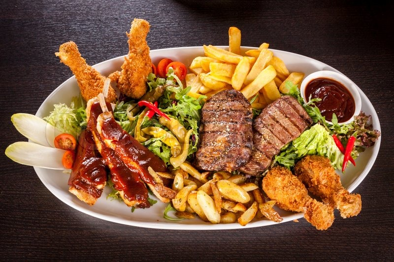 Wholesome platter of mixed meats including grilled steak, crispy crumbed chicken and beef on a ...
