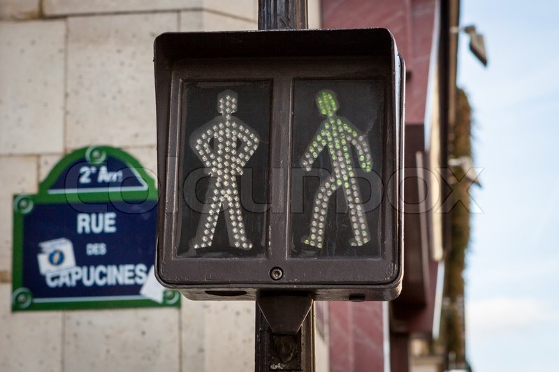 Pedestrian traffic lights at an intersection showing a figure standing and walking which will illuminate green to allow pedestrians to cross the street or red to warn them to wait before crossing, stock photo