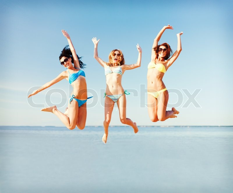 Summer holidays and vacation - girls jumping on the beach, stock photo