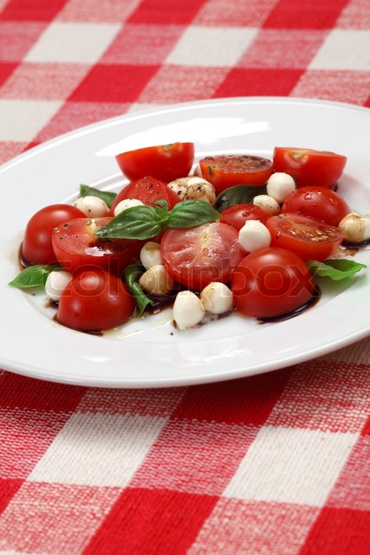 Stock image of 'Photo of a Caprese salad with tomato, mozzarella, basil, balsamic and olive oil. '