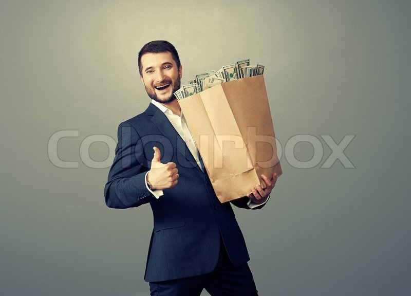 Excited businessman holding paper bag with money, showing thumbs up and smiling. photo in studio over grey background, stock photo