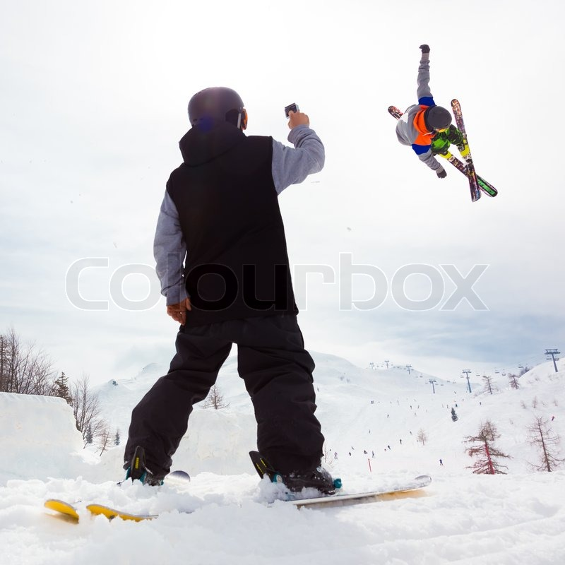 Free style skier performing a high jump. Buddy filming it on a Gopro camera. Ski lifts in the mountains in the background, stock photo