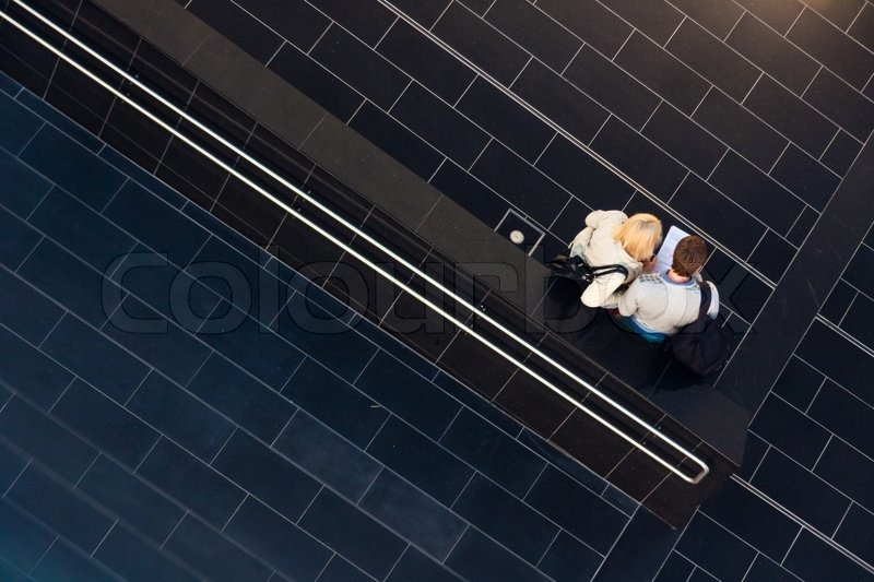 Couple reviewing the decision on child adoption on the tiled hallway, stock photo