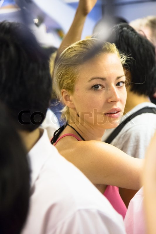 Blonde caucasian lady traveling by public transport. Lonely in the crowd, stock photo