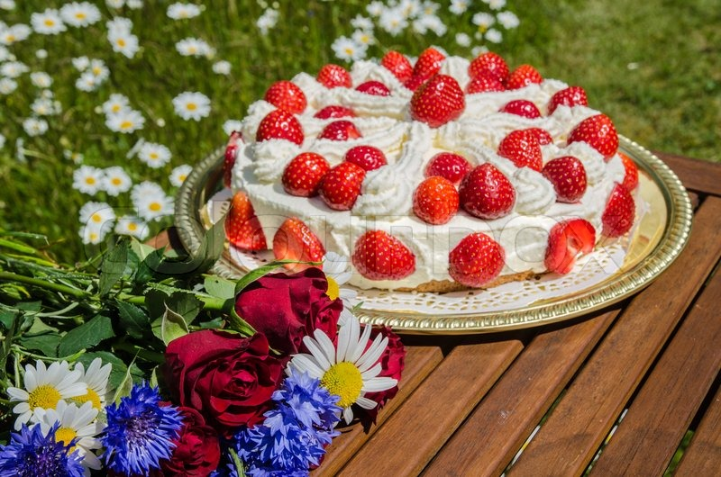 Bouquet of summer flowers at a table with homemade strawberry cake ...