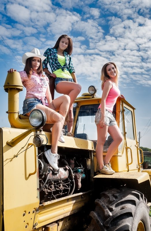 Three Sexy Attractive Woman Standing On Old Big Tractor