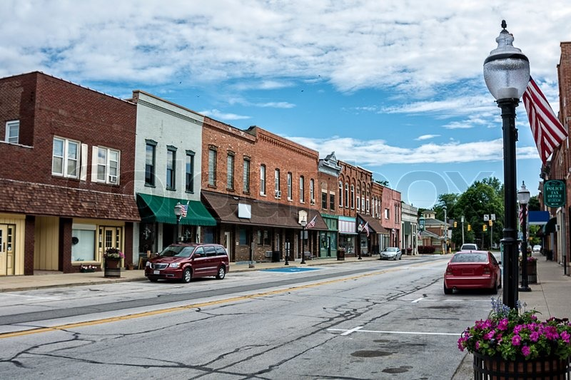 A photo of a typical small town main street in the United States of America. Features old brick buildings with specialty shops and restaurants. Decorated with spring flowers and American flags, stock photo
