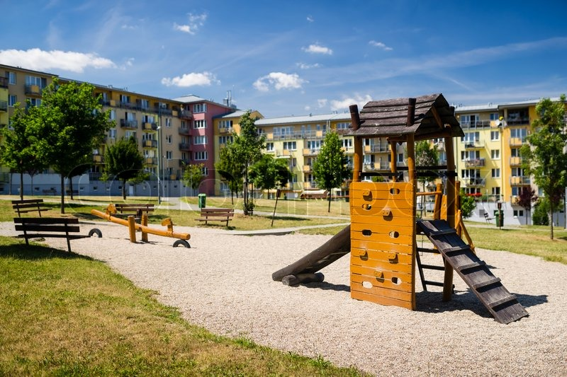 Children playground in nature in front of row of newly built block of flats, stock photo