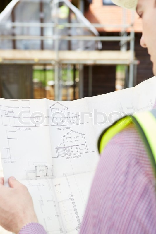 Architect On Building Site Looking At Plans For House, stock photo