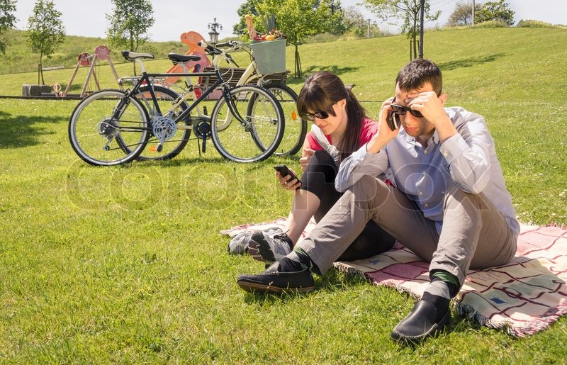 Relaxed couple in love using a smartphones sitting on the grass park at sunny summer day, stock photo