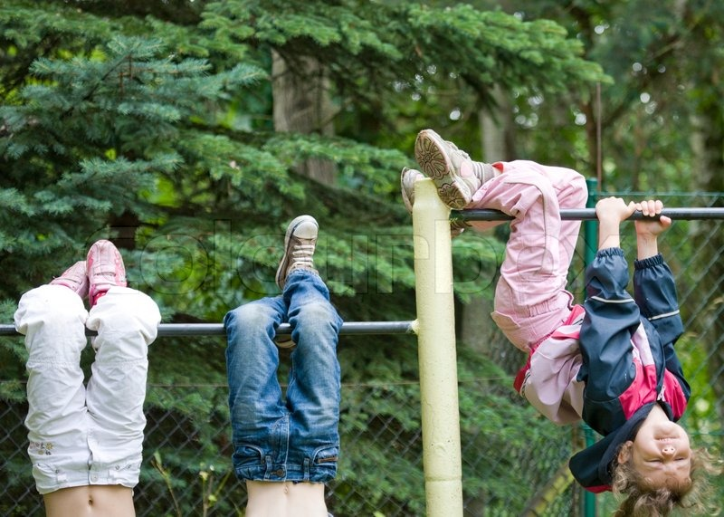 Children hanging upside down on a playground pole | Stock ...
