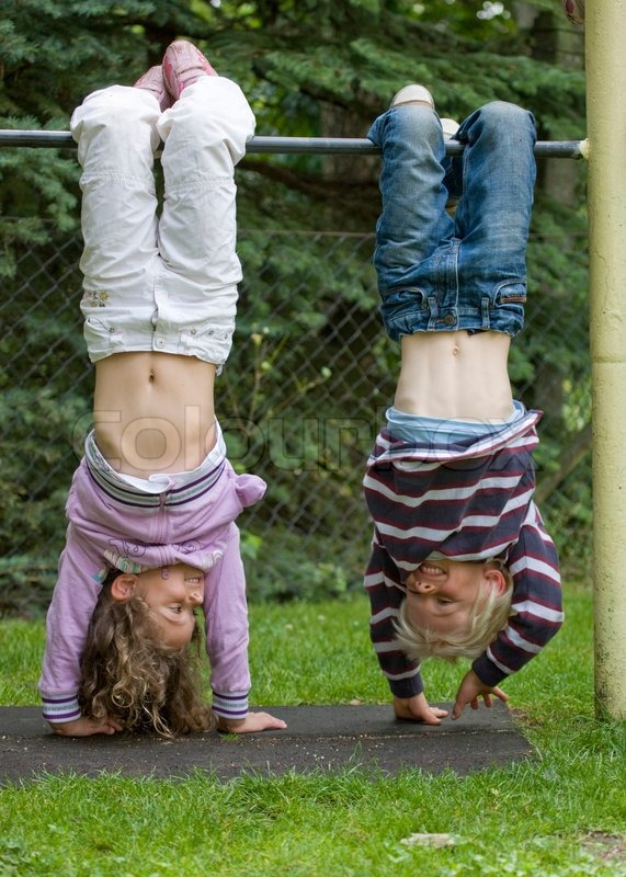 Children hanging upside down in a playground pole | Stock ...