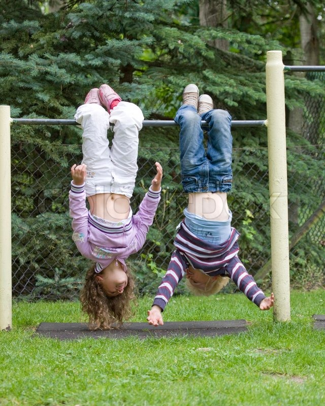 Two children hanging upside down on a ... | Stock Photo ...
