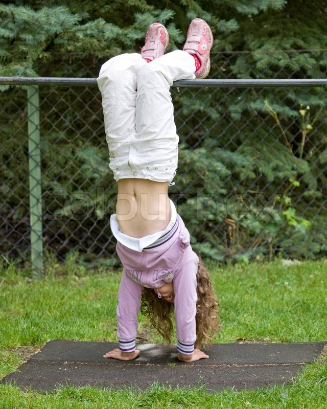 A girl hanging upside down on a playground pole | Stock ...