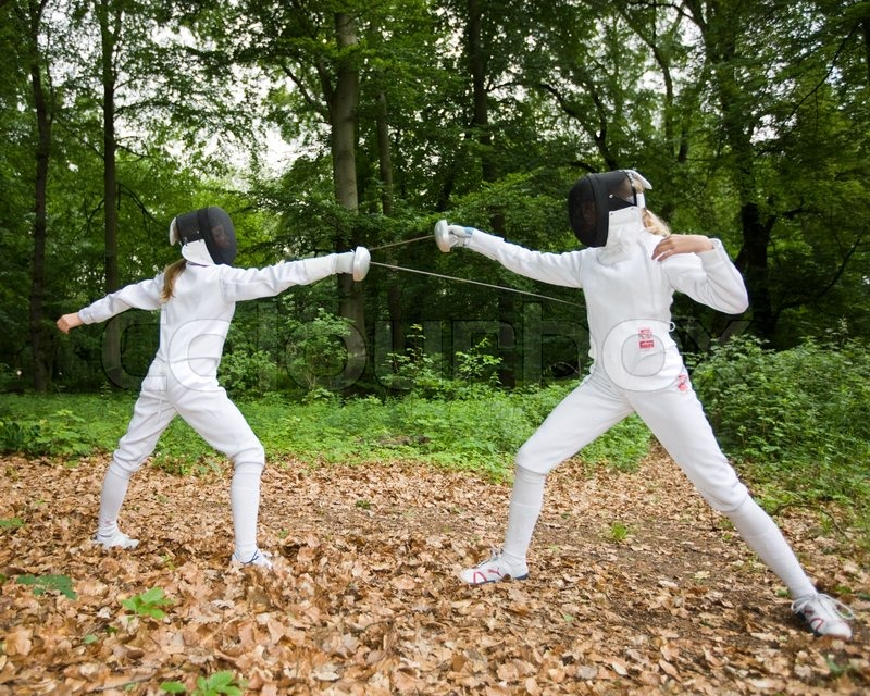 Two Girls Practice Fencing In The Woods Stock Photo