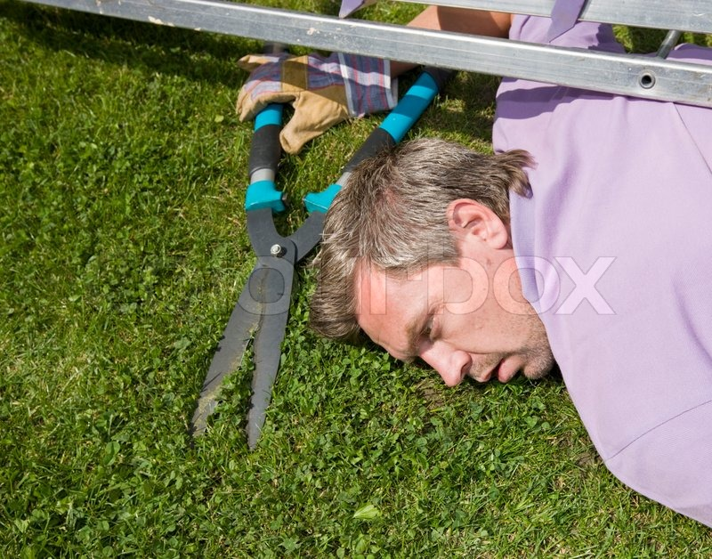 A man in a garden with a big garden scissors having a heart attack